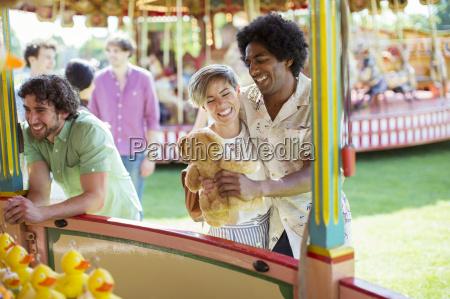 smiling couple holding teddy bear next