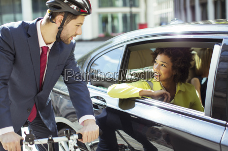 businessman on bicycle talking to woman