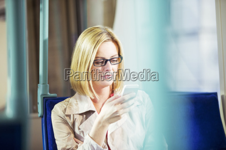 businesswoman using cell phone on train