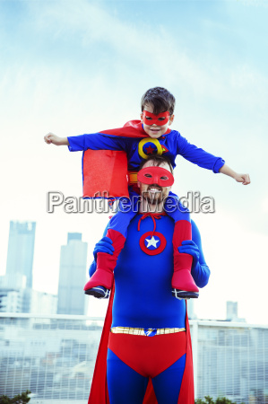 superhero father carrying son on shoulders