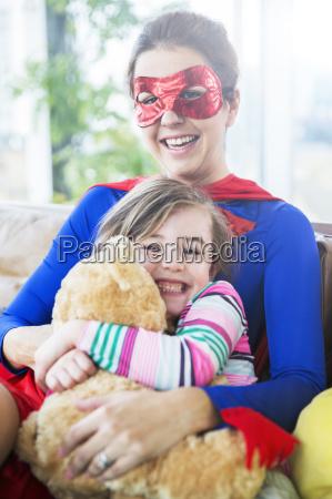 superhero mother hugging daughter on sofa