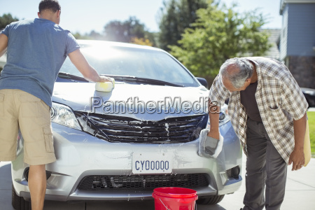 father and son washing car in