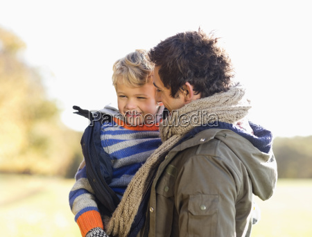 father carrying son outdoors