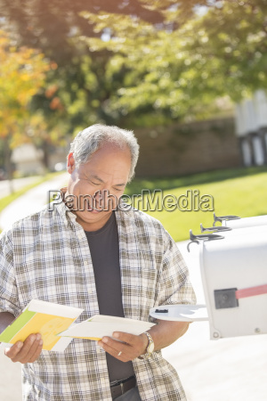 man retrieving mail at mailbox