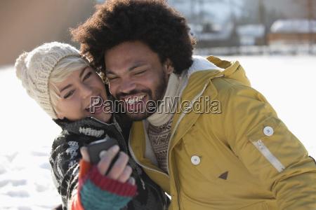 happy couple taking selfie in snow