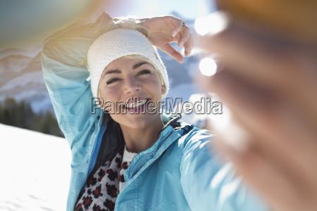 happy woman taking selfie in snow