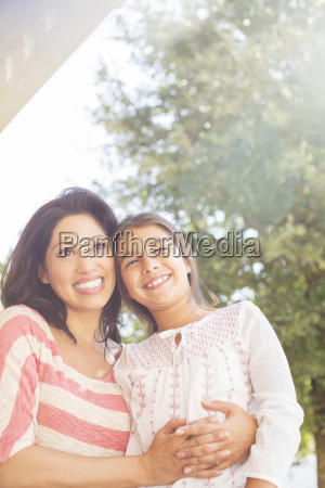 smiling mother and daughter outdoors