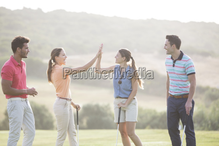 friends high fiving on golf course