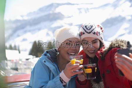 friends in warm clothing taking selfie