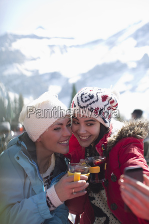 smiling women in warm clothing drinking