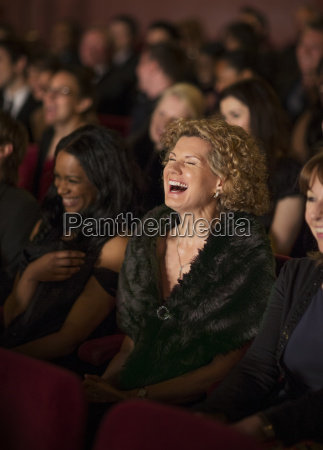 woman laughing enthusiastically in theater audience