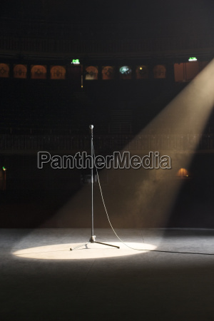 microphone in spotlight on empty theater