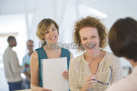 office workers chatting and laughing during