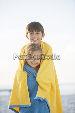 brother and sister wrapped in towels