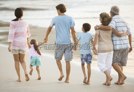 multi generation family holding hands on
