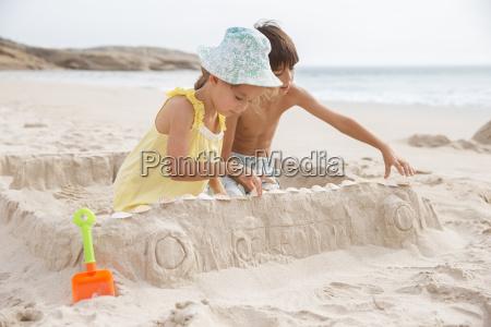 children making sandcastle on beach
