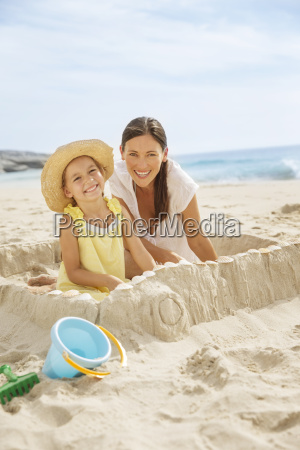 mother and daughter making sandcastle on