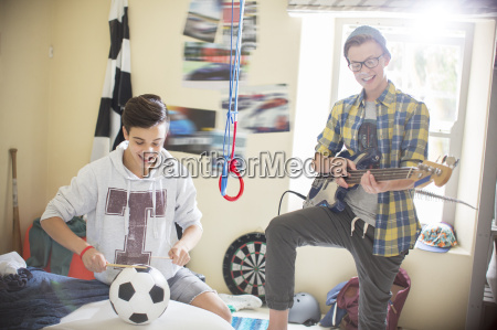 two teenage boys playing music in