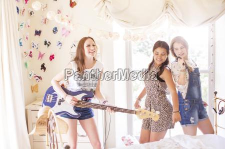 three teenage girls playing music and