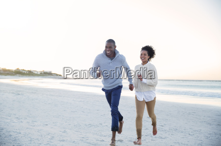 couple holding hands and running on