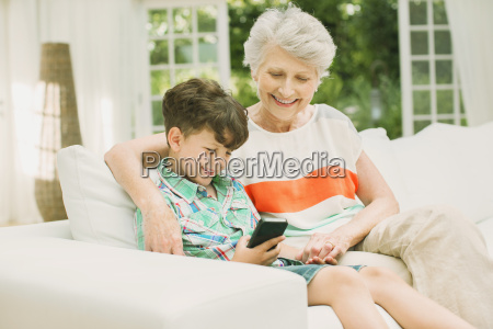 older woman and grandson using cell