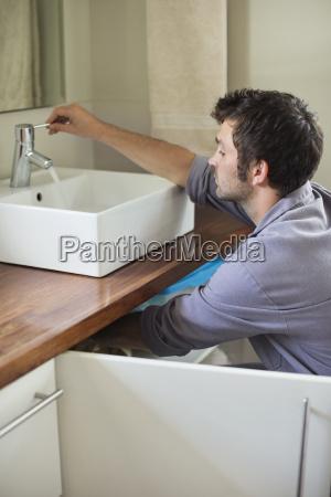 plumber working on bathroom sink