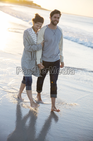 young couple walking on beach in