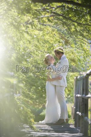 young couple embracing on wooden bridge