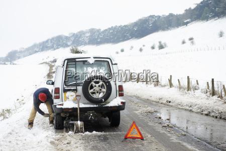 man working on broken down car