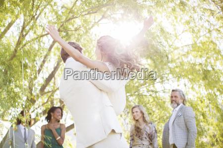 bridegroom picking bridesmaid up at wedding