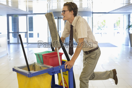 businessman pushing cleaning cart in office