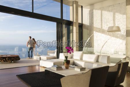 couple standing on balcony of modern