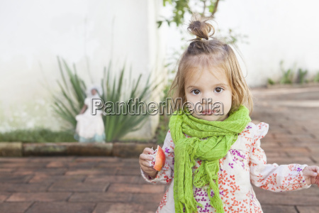 baby girl eating fruit outdoors