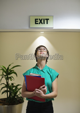 businesswoman standing under office exit sign