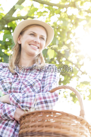 smiling woman in hat holding basket