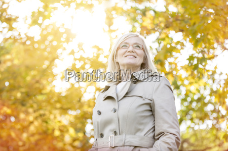 smiling senior woman under sunny autumn
