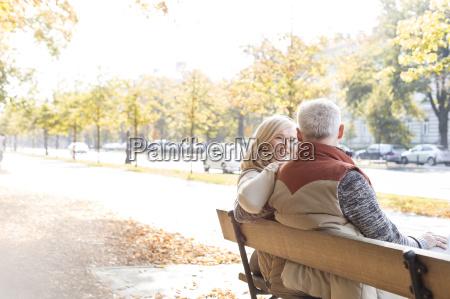 senior couple hugging on bench in
