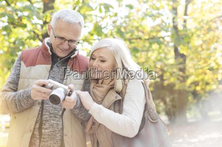 senior couple using digital camera in