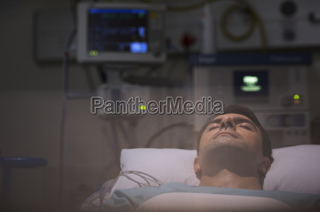 patient lying in bed surrounded by