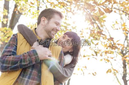 smiling couple hugging under sunny autumn