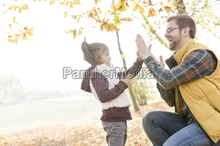 father and daughter playing patty cake