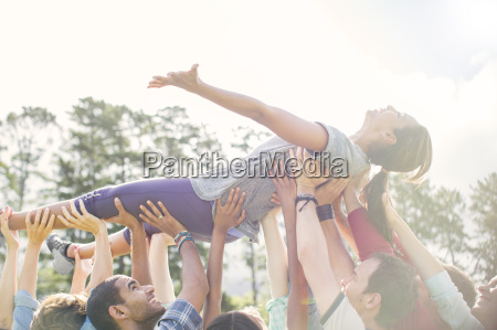 carefree woman crowdsurfing supported by team