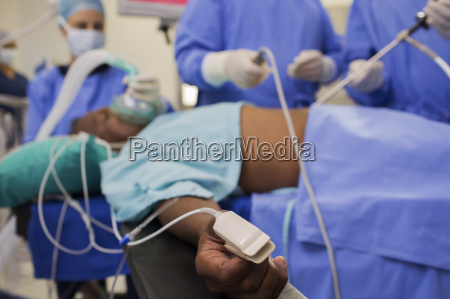 doctors performing laparoscopic surgery patient with