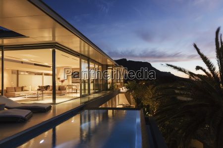 modern house overlooking mountains at dusk