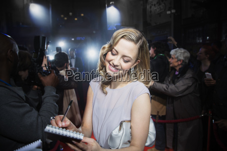 well dressed female celebrity signing autographs