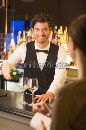well dressed bartender pouring wine for