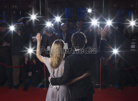 rear view of celebrity couple waving