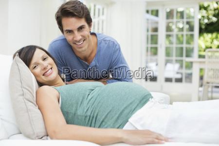 man sitting next to pregnant woman