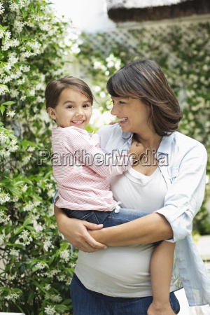 pregnant mother holding daughter outdoors
