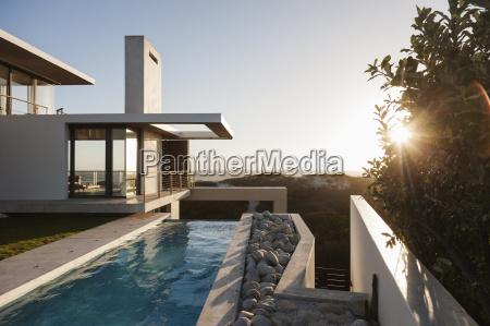 modern house overlooking beach at sunset